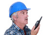 A foreman talking on a walkie-talkie.