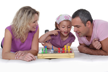 Little girl learning chess with her parents.