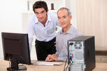 a young man and a senior man behind a computer