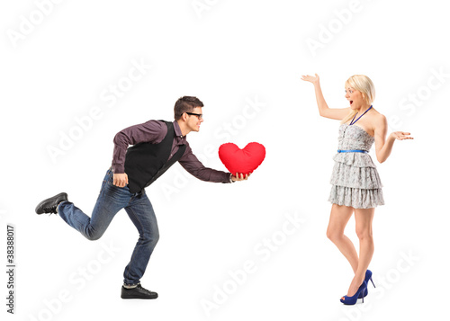 A man running with a red heart shaped pillow in his hand and an