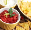 Bowl of salsa with nachos and sour cream