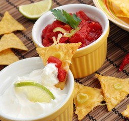 Tortilla chips with dips including salsa and sour cream