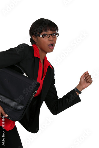 An African American businesswoman running.