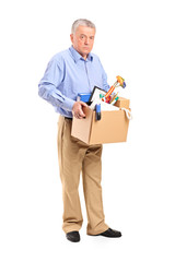 Full length portrait of a fired man carrying a box of personal i