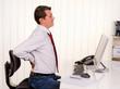 Mann im Büro mit Rückenschmerzen