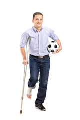 Full length portrait of an injured young man on crutches holding