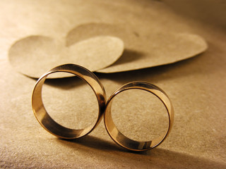 Gold wedding rings and paper hearts over paper sheet
