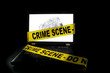 Laptop computer with crime scene tape across it