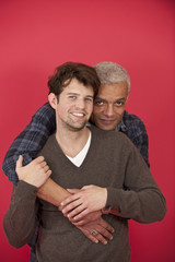 Gay couple hugging on red background