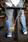 Glass blower shaping molten glass into a drinking goblet