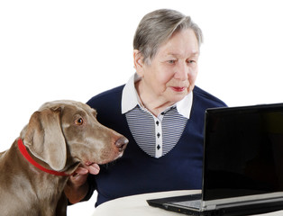 senior woman with dog working on a laptop