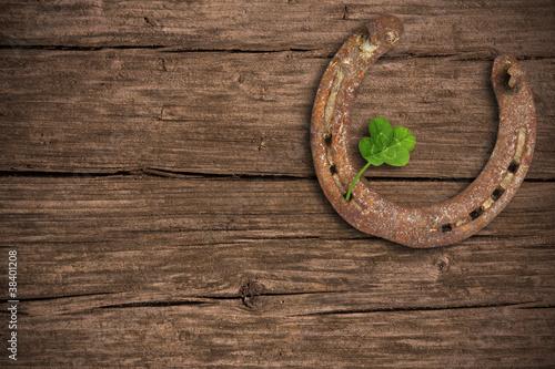 Hufeisen und Kleeblatt auf Holzhintergrund