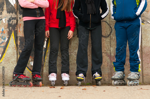 Group of teenagers in roller skates standing beside the wall