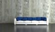 Wohndesign - Sofa mit blauen Kissen vor Betonwand