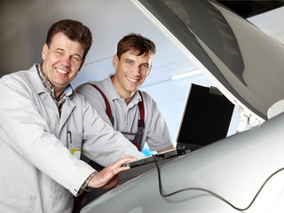 Motor mechanics checking the engine bay with diagnostic computer