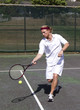 Male tennis player makes a forehand swing
