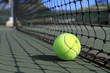 Tennis ball lies next to a net on the court