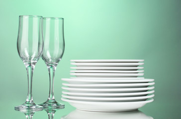 Clean plates and glasses on green background