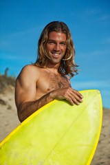 Long haired blonde surfer and surfboard.