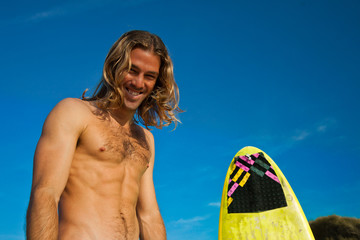 Long haired blonde surfer laughing and surfboard.