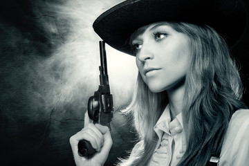 Beautiful girl with in a hat, with a revolver