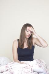 Frau mit Kater im Bett sitzend