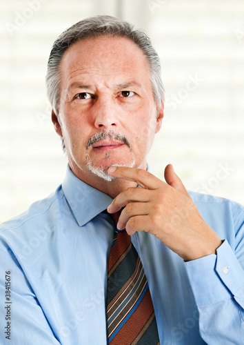 Senior businessman thinking at something