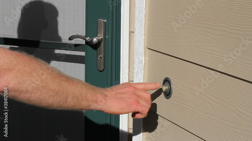 Man Ringing Front Door Bell of a Home on a Sunny Summer Day