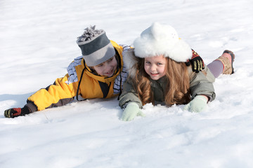 Happy children laying down in the snow