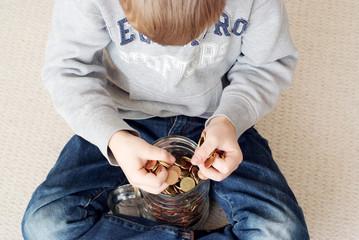 Junge sitzt über seinem Ersparten