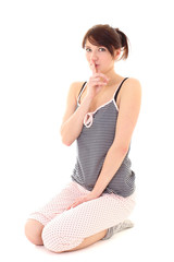 girl in pajamas showing shhh sign