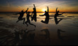 silhouette of friends jumping on beach during sunset