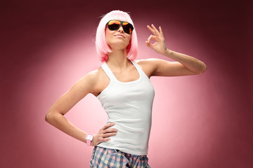 Young girl in pink wig posing for camera across pink background