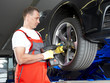 Motor mechanic in a garage is changing a tyre