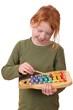 Junges rothaariges Mädchen musiziert auf einem Spielzeugxylophon
