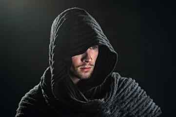 A bearded man in a hood.