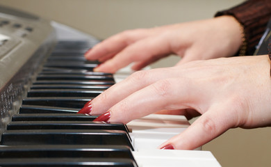 Close up of the hands of a woman playing piano