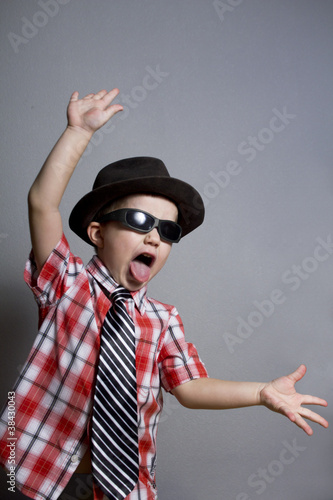 The boy in a hat and black glasses on a gray background