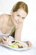 portrait of lying down woman eating salad