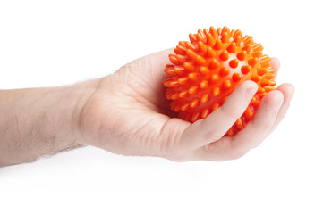 Man hand with Spiny plastic orange massage ball isolated on whit