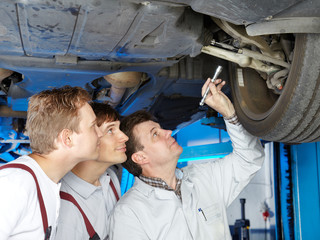 Master mechanic and his employees checking a car