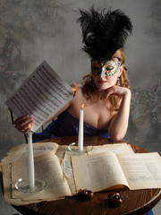 Girl in mask burns paper at a candle flame