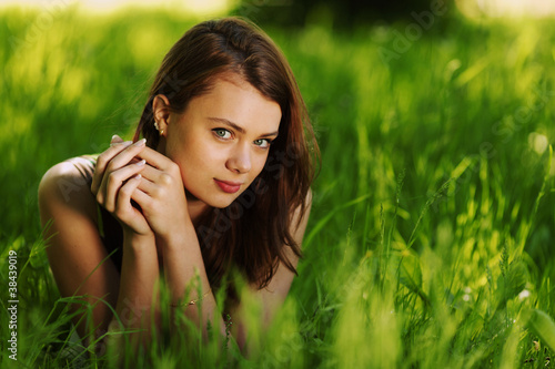 brunette lying on green grass