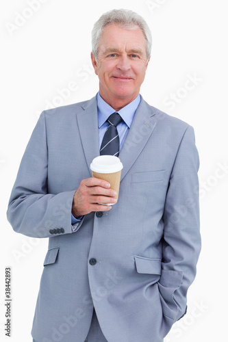 Smiling mature tradesman with paper cup
