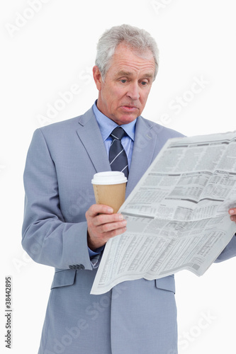 Surprised mature tradesman with news paper and paper cup
