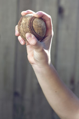 A child holds a used baseball