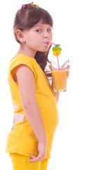 Beautiful little girl drinking orange juice