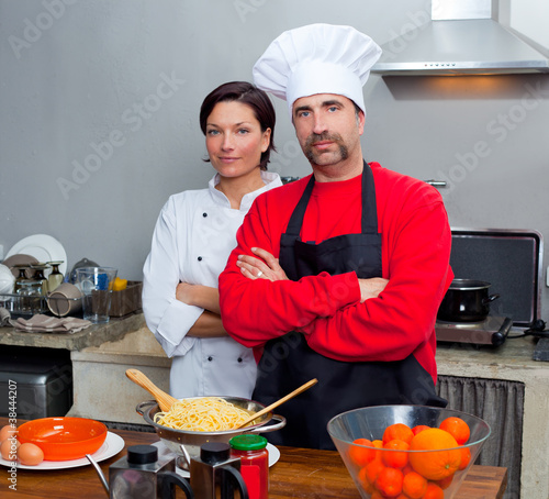 Chef couple man and woman posing in kitchen