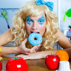Blonde funny girl on kitchen eating blue dona