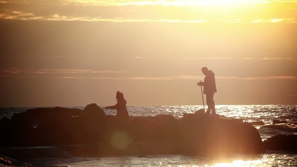 A man and a woman fishing in the sea at sunset
